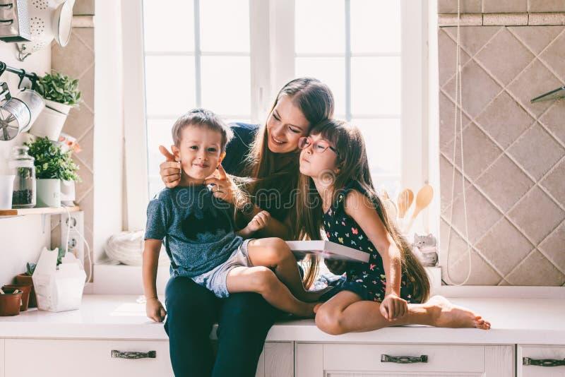 Мама при дети есть на кухонном столе стоковое изображение
