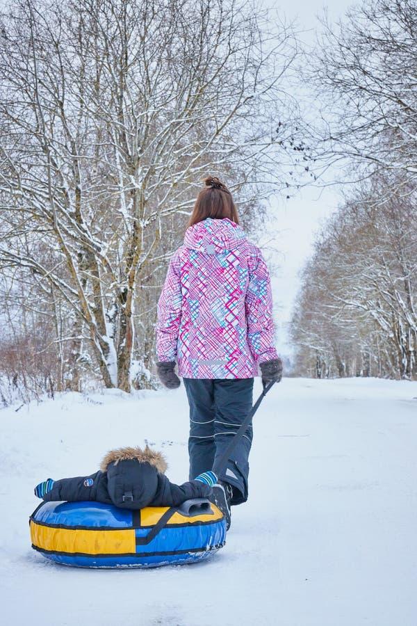 Мама свертывает ее меньшего сына на трубопроводе в парке в зиме семья счастливая outdoors потеха зимы для маленьких ребят стоковое изображение