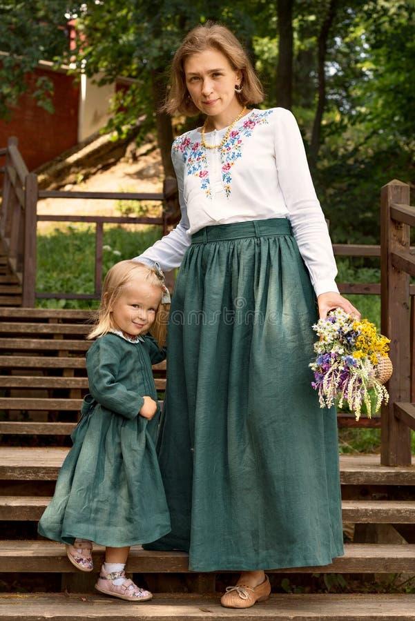 Мама семьи с дочерью в винтажном ретро белье стиля одевает с лестницами рассвета букета идя деревянными в саде парка стоковая фотография