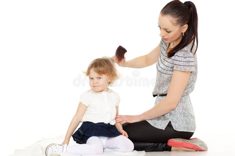 Мама смотрит после волос ребенка. стоковые изображения rf