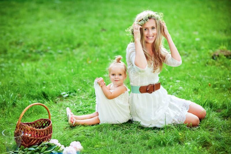 Мама с венком на его голове и дочь сидят на gr стоковое изображение rf