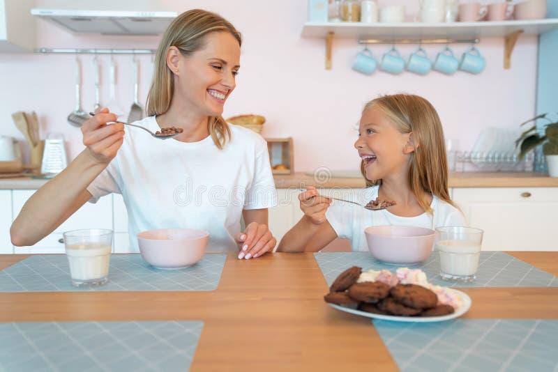Мама с дочерью ест шоколадные хлопья они держат ложки в рот, смотрят друг на друга и улыбаются хорошо провести время стоковое фото