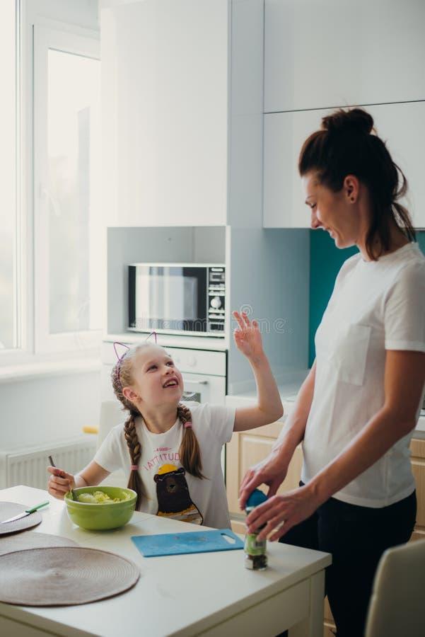 Мама с ее дочерью варит в кухне, серии фото образа жизни в ярком домашнем интерьере стоковые изображения rf