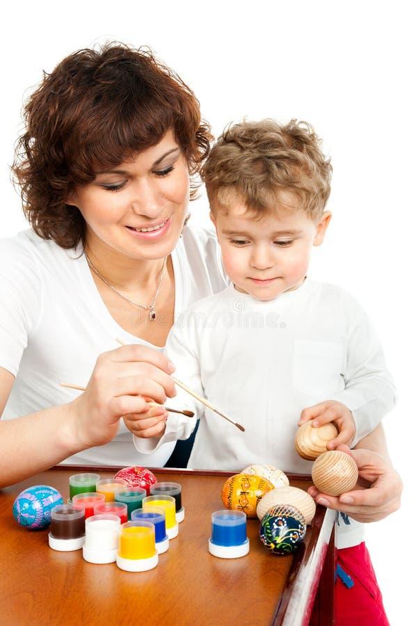 Мама с ее сыном украшает пасхальные яйца стоковая фотография