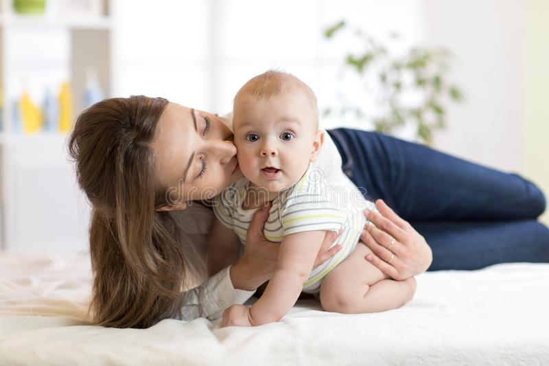 Мама целуя ее маленького сына на кровати Младенец матери обнимая младенческий стоковое фото