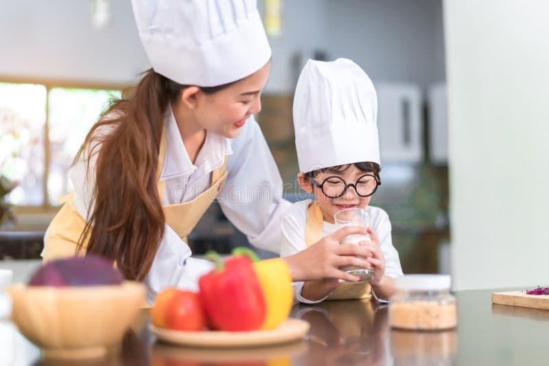 Мама шеф-повара азиатская помогая меньшему питьевому молоку сына для здорового в комнате кухни стоковые изображения
