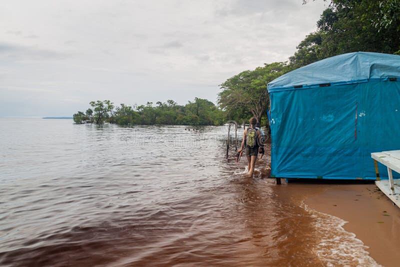 МАНАУС, БРАЗИЛИЯ - 25-ОЕ ИЮЛЯ 2015: Турист на пляже da Ponta Negra Прая во время leve прилива стоковые изображения