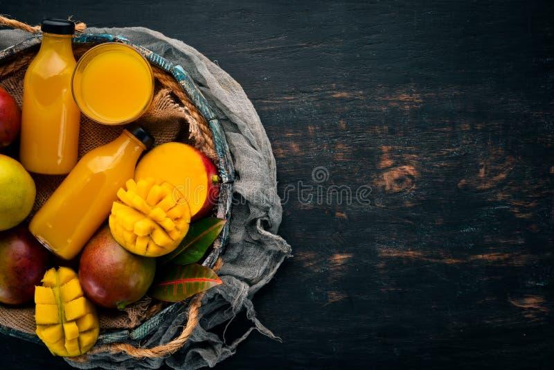 Манго и сок в деревянной коробке На деревянной предпосылке Тропические плоды стоковое изображение