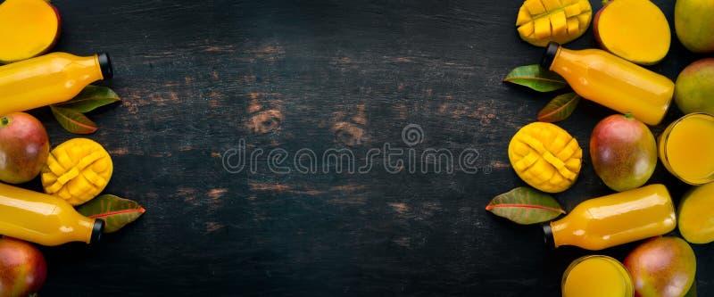 Манго с листьями на черной деревянной предпосылке Тропические плоды стоковая фотография