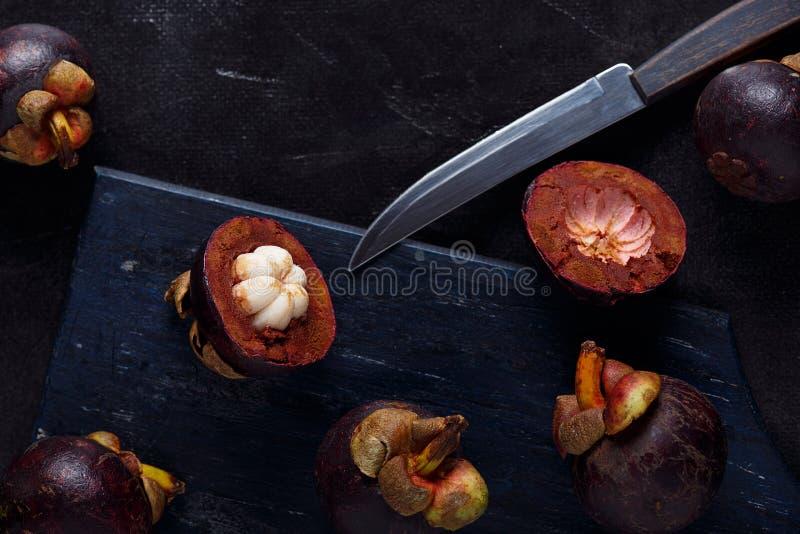 Мангустан и поперечное сечение показывая толстую пурпурную плоть кожи и белых ферзя плодов, очень вкусного плода мангустана стоковое изображение rf