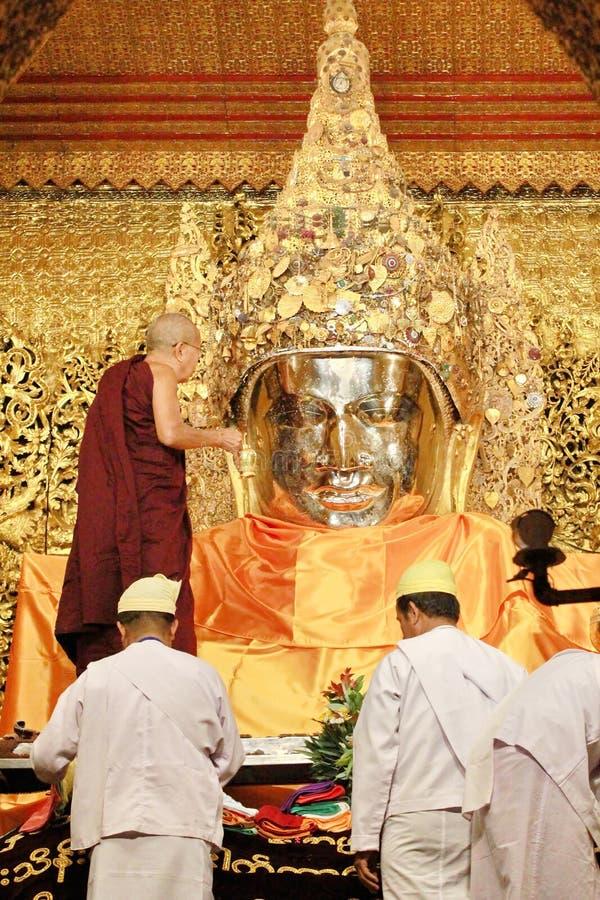 МАНДАЛАЙ, МЬЯНМА - 3,2018 -ГО ФЕВРАЛЬ: Старший монах быть мытья стороны к изображению Mahamuni Будды на виске Mahamuni Будда и стоковые изображения