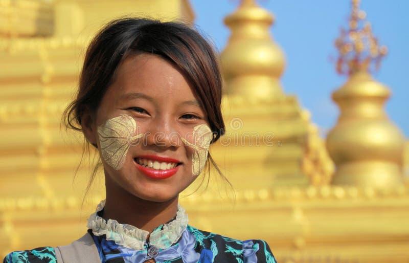 МАНДАЛАЙ, МЬЯНМА - 17-ОЕ ДЕКАБРЯ 2015: Портрет бирманской девушки с традиционным Thanaka смотрит на картину перед золотой пагодой стоковое изображение