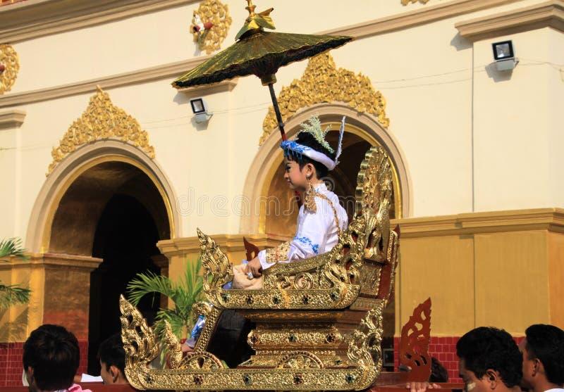 МАНДАЛАЙ, МЬЯНМА - 18-ОЕ ДЕКАБРЯ 2015: Церемония Shinbyu новициата Novitiation для молодого буддийского мальчика на стуле седана  стоковые изображения