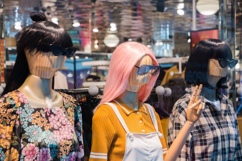 Манекены с современными одеждами в окне дисплея магазина моды стоковые фотографии rf