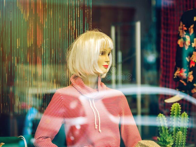 Манекен внутри магазина, взгляд женщины через окно стоковые фотографии rf