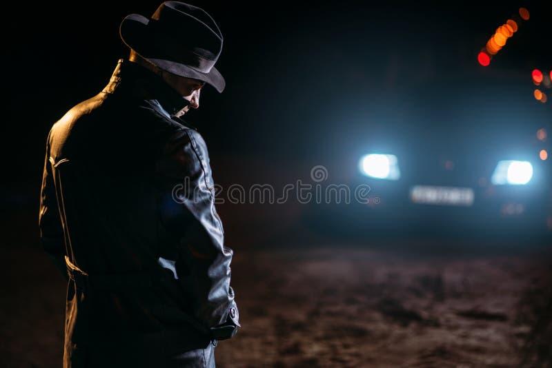 Маниак в черных кожаных пальто и шляпе, заднем взгляде стоковые изображения rf