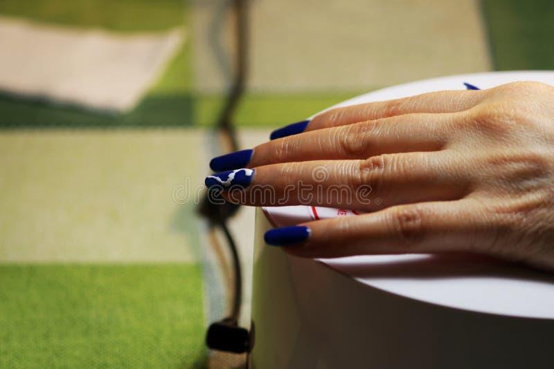 маникюр выполненный студентом рука лежит на специальной лампе ультрафиолетова Голубая отделка с покрашенной белой молнией стоковые фотографии rf