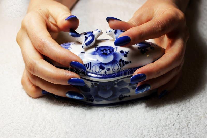 маникюр выполненный студентом руки лежат на белой коробке фарфора, покрашенной в стиле Gzhel Голубая отделка с болью стоковые изображения