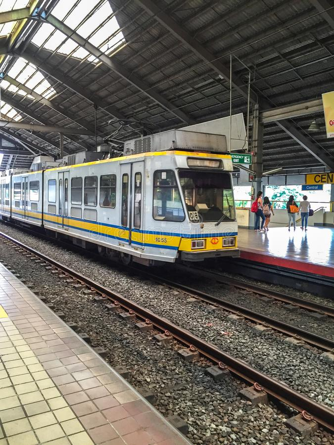 Манила, Филиппины - 19-ОЕ ИЮЛЯ 2015: Поезд LRT приезжает на вокзал в Манилу, Филиппины LRT служит 579 000 пассажиров стоковые изображения