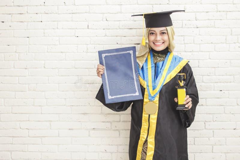 Мантия градации счастливой градуированной студентки нося держит d стоковая фотография rf