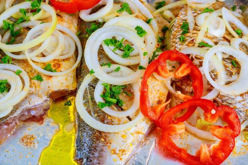 Маринад прикладной к части на камне шифера на металлической предпосылке Подготовка для варить еду рыб стоковые фото