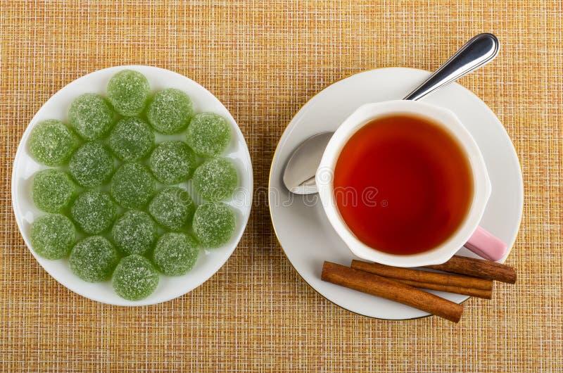 Мармелады в плите, циннамоне, чайной ложке, чашке чаю на поддоннике на циновке Взгляд сверху стоковая фотография