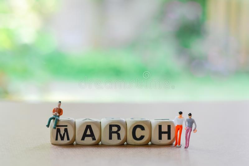 марш на деревянных блоках миниатюры, небольшой человек-модель, стоящий на полу с зеленым размытым фоном Копировать пространство д стоковые изображения rf