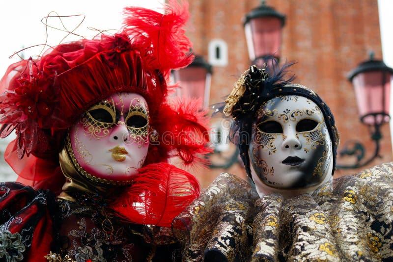 Маска и костюм красно-черн-золота пар масленицы на традиционном фестивале в Венеции, Италии стоковая фотография