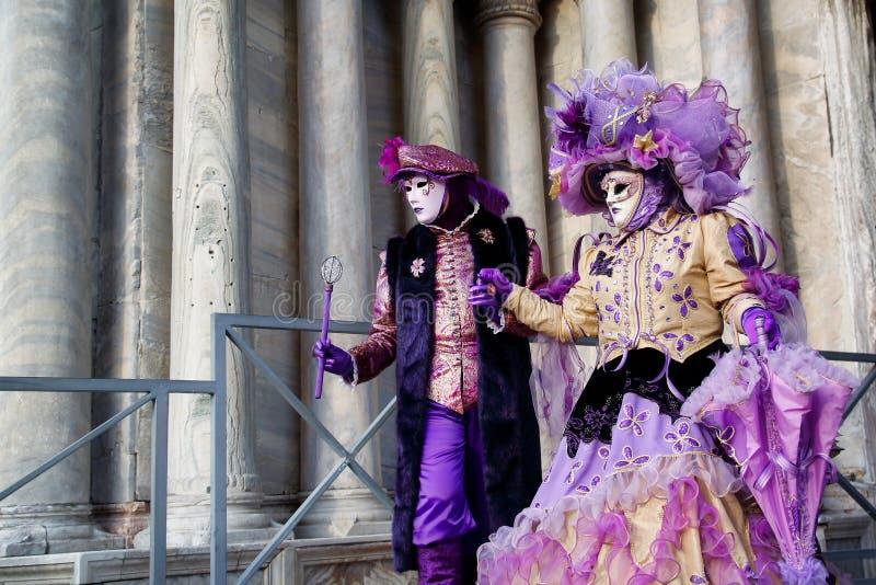 Маска и костюм красочной масленицы пар пурпурн-бежевая на традиционном фестивале в Венеции, Италии стоковые фотографии rf