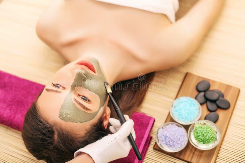 Маска курорта Женщина в салоне спы Лицевой щиток гермошлема Лицевая маска глины стоковые фото