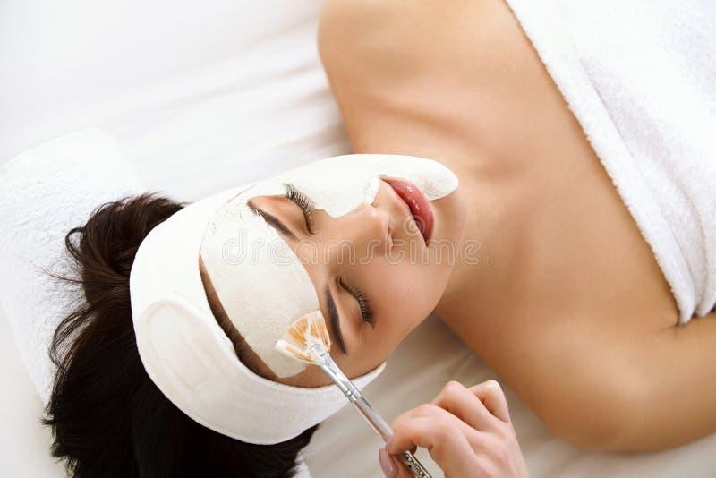 Маска курорта. Женщина в салоне курорта. Лицевой щиток гермошлема. Лицевая маска глины. стоковое фото