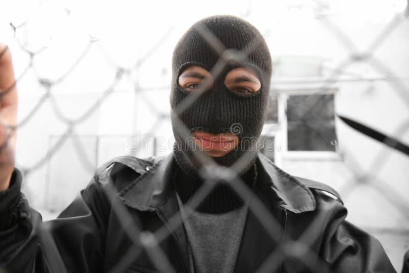 Маска мужского похитителя нося и с ножом около загородки сетки outdoors стоковые изображения rf