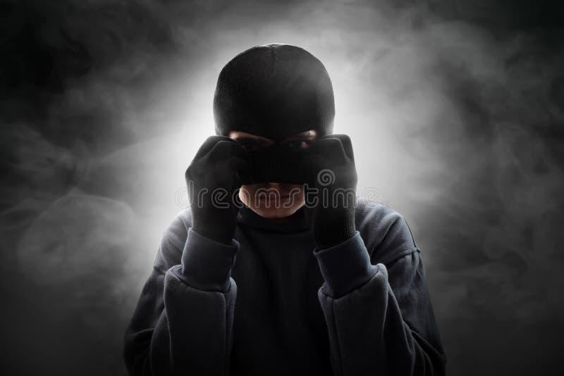 Маска похитителя нося на предпосылке дыма стоковая фотография