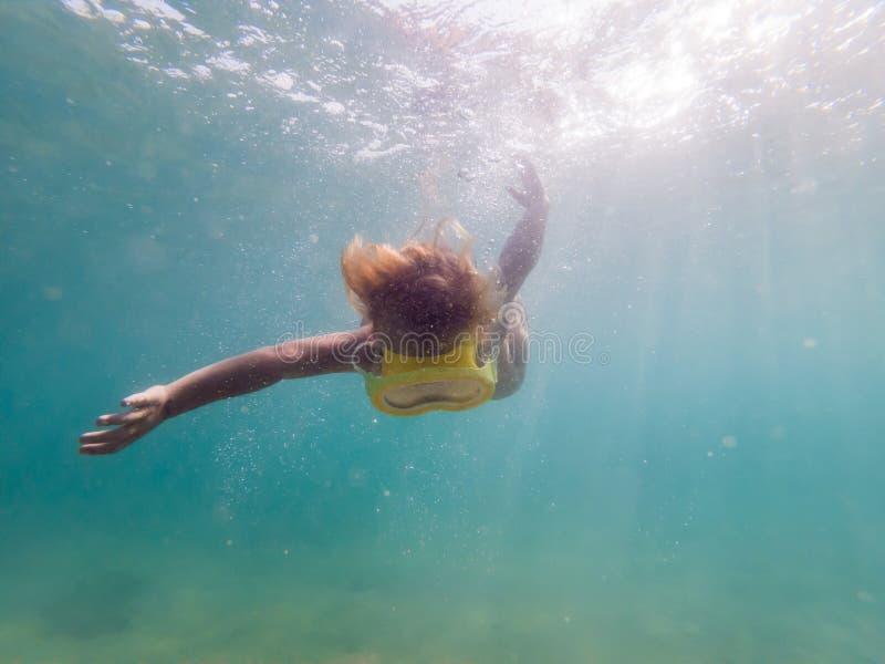 Маска ребенка нося snorkeling ныряя под водой стоковое изображение rf
