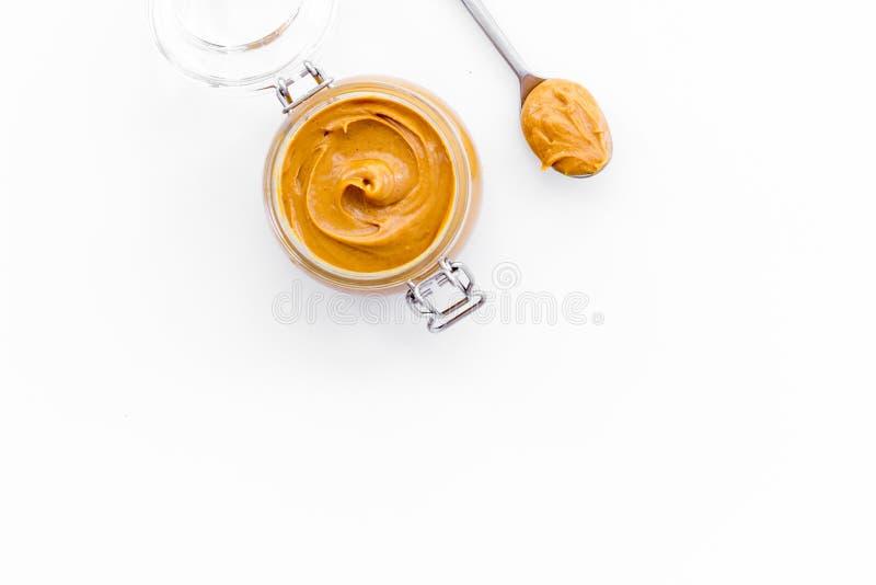 Масло гайки, арахисовое масло в стеклянном опарнике и ложка с маслом на белом взгляд сверху предпосылки копируют космос стоковое изображение rf