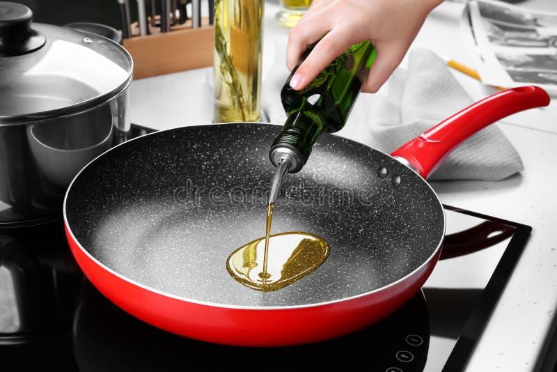 Масло женщины лить от бутылки в сковороду стоковое фото