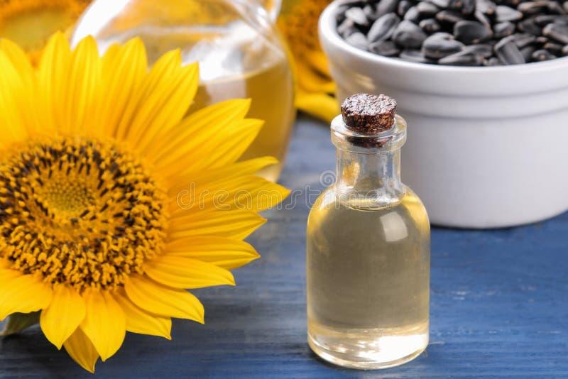 Масло и семена подсолнуха семян подсолнуха с красивыми желтыми солнцецветами на заднем плане на голубой деревянной предпосылке стоковое изображение rf