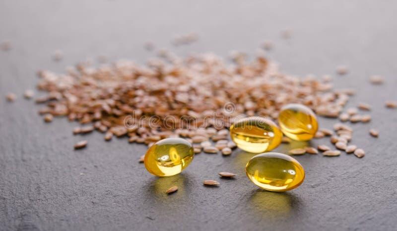 Масло льняного семени в крышках на серой предпосылке стоковые фотографии rf