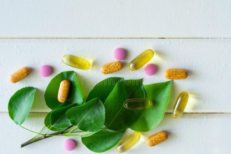 Масло, таблетки и витамин рыбной ловли омеги капсул на зеленых лист стоковые изображения rf