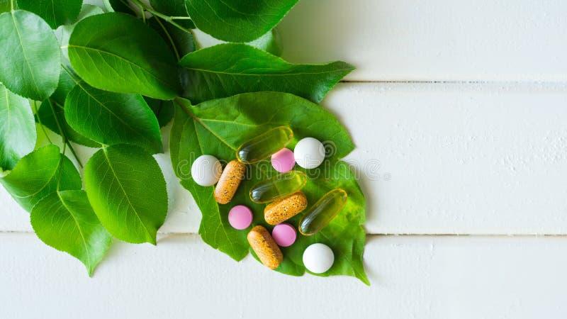 Масло, таблетки и витамин рыбной ловли омеги капсул на зеленых лист стоковые изображения