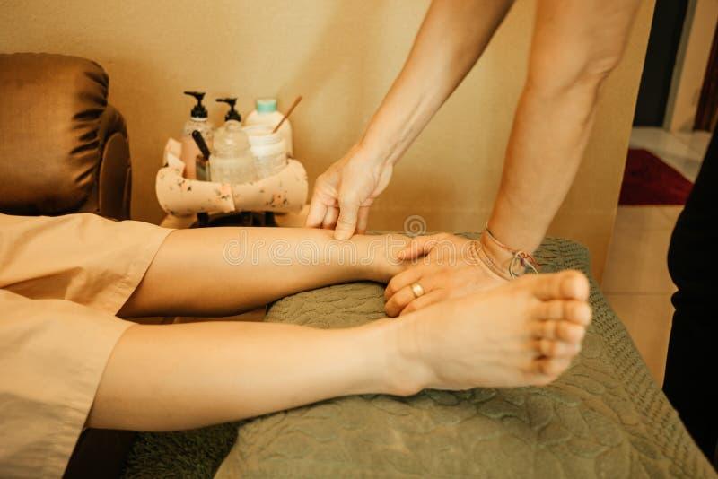 Массажируйте массаж тела предпосылки в молодой женщине салона курорта срочной стоковая фотография