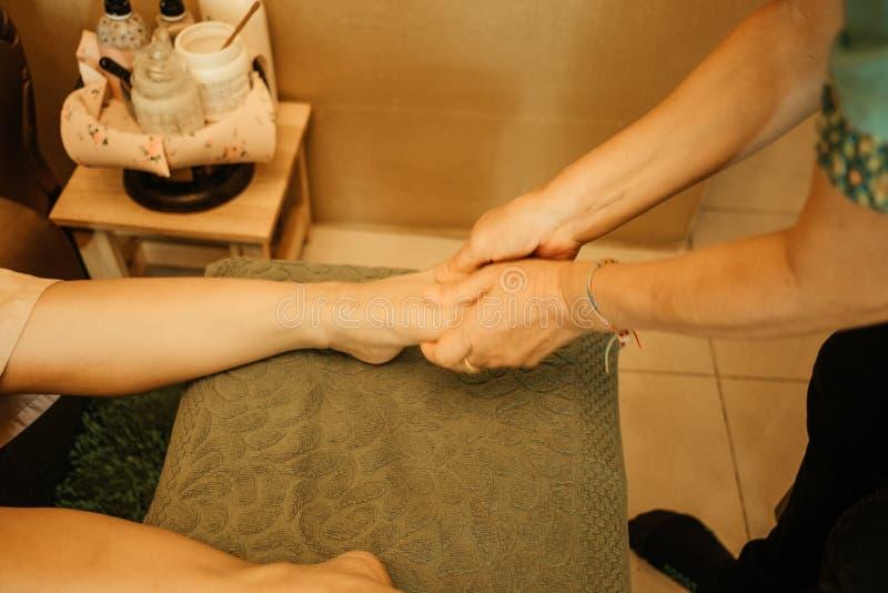 Массажируйте массаж тела предпосылки в молодой женщине салона курорта срочной стоковое фото rf