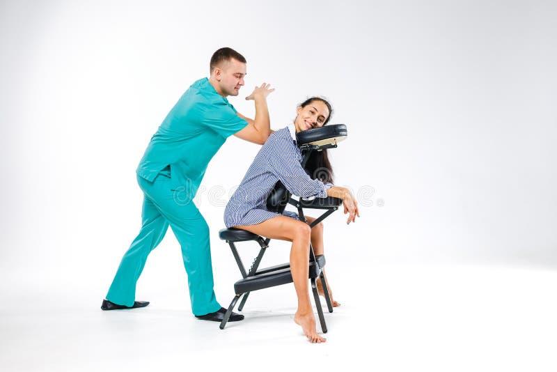 Массаж и офис темы Мужской терапевт с голубым костюмом делая массаж для работника молодой женщины, дело задней части и шеи стоковые фотографии rf