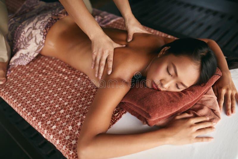 массаж тайский Женщина имея массаж задней части релаксации на салоне спа стоковое фото rf