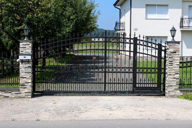 Массивные черные чугунные входные двери с украшениями, который держат на месте 2 каменных поляка с уличными фонарями стиля барокк стоковая фотография rf