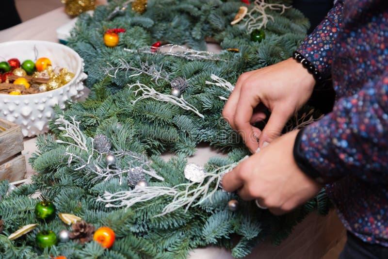 Мастерская венка рождества сплетя Руки женщины украшая венок праздника сделанный елевых ветвей, конусов и различного органическог стоковые фото