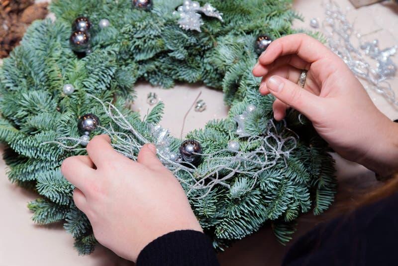 Мастерская венка рождества сплетя Руки женщины украшая венок праздника сделанный елевых ветвей, конусов и различного органическог стоковые изображения