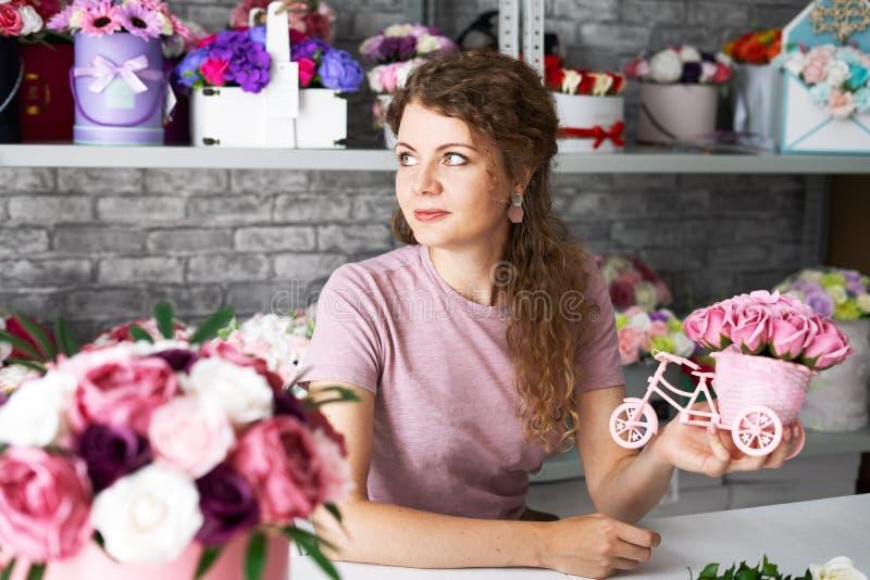 Мастерская цветка: девушка флориста делает букеты из цветков в коробках для того чтобы приказать стоковые фото