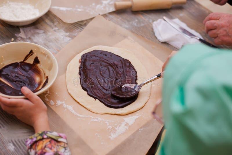 Мастерский класс для детей на пироге выпечки Маленькие ребеята учат сварить сладостный пирог Дети подготавливая домодельный пирог стоковая фотография