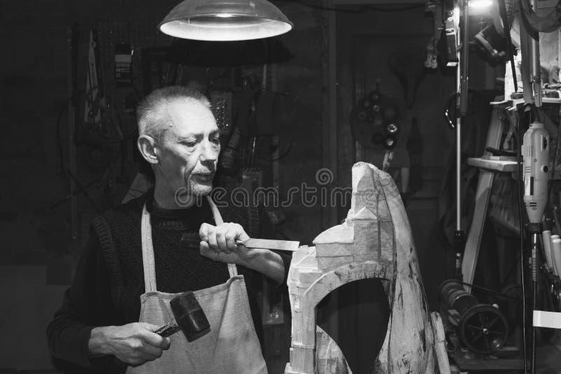Мастерский плотник работая в его мастерской работы по дереву стоковое фото